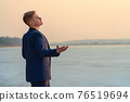 A young guy expresses emotions, on the seashore, sings and gestures. Against the backdrop of the sunset sea. 76519694