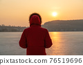 A young man in a red jacket, in the winter on the frozen sea, stands with his back in thought. Against the background of a sunset. 76519696