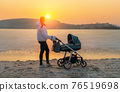 A young mother walks with a stroller for a baby on the shore of a frozen lake, at sunset. 76519698