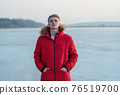 A young guy teenager, in a red jacket, poses and reflects emotionally about life, against the background of a frozen lake. 76519700