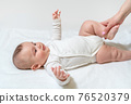 Newborn healthy baby doing physical exercises for the legs and hip joint. With the help of the medic's mom. On white background. 76520379