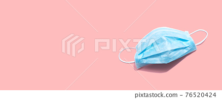 Blue surgical mask overhead view 76520424
