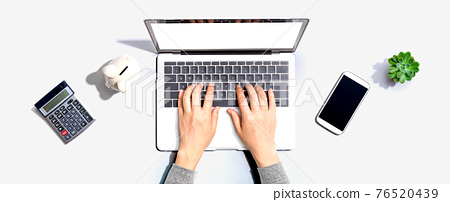 Woman using a laptop computer with a piggy bank 76520439
