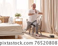 Elderly man practicing yoga asana warrior using chair 76520808