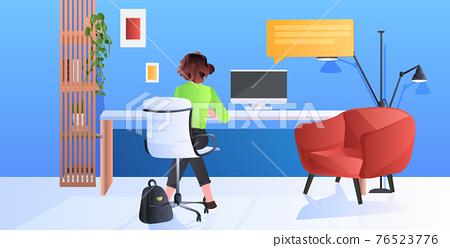 woman sitting at workplace and using computer chat bubble communication concept full length 76523776