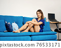Pretty young woman sits on sofa at home 76533171