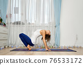 Young woman practicing yoga at home stands on toes and fingers 76533172