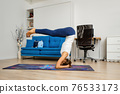 Young woman practicing yoga at home, stands in supported headstand with bent legs 76533173