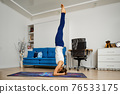 Young woman practicing yoga at home, doing supported headstand 76533175