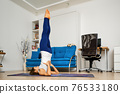 Woman does supported shoulderstand yoga pose 76533180