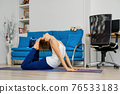 Woman practicing yoga at home, does bow pose 76533183