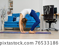 Young woman practicing yoga at home, doing inversion pose 76533186