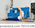 Portrait of young woman doing cobra yoga pose at home 76533188
