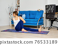 Portrait of young woman doing yoga marichi pose 76533189
