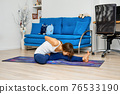 Full length portrait of young woman doing yoga pose on a floor 76533190