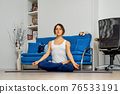 Young woman practicing youga at home sitting in easy pose 76533191