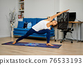 Young woman practicing yoga at home, stretching arm and leg 76533193