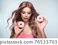 Beautiful woman with pink hair, beautiful makeup with donuts in her hands posing in the studio. 76533703