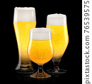 Set of fresh light beer glasses with bubble froth isolated on black background. 76539575