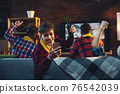 Group of friends watching TV, sport match together. Emotional man cheering for favourite team, celebrating successful betting. Concept of friendship, leisure activity, emotions 76542039