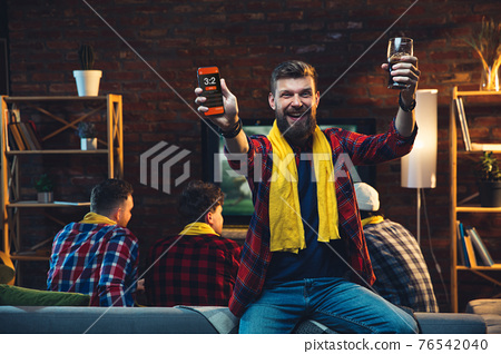 Group of friends watching TV, sport match together. Emotional man cheering for favourite team, celebrating successful betting. Concept of friendship, leisure activity, emotions 76542040