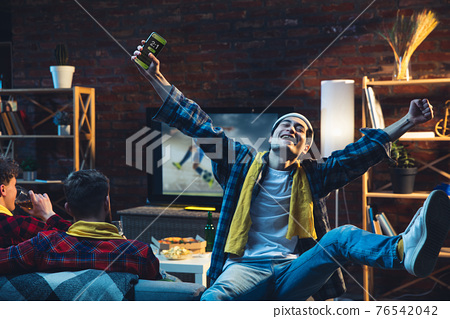 Group of friends watching TV, sport match together. Emotional fans cheering for favourite team, watching on exciting game. Concept of friendship, leisure activity, emotions 76542042