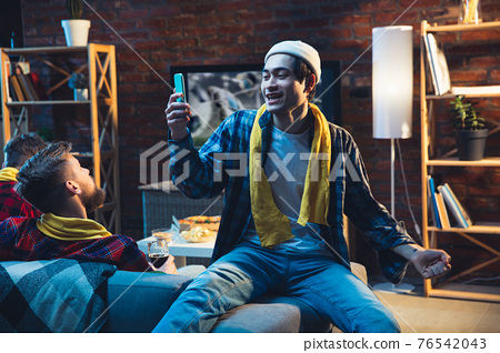 Group of friends watching TV, sport match together. Emotional fans cheering for favourite team, watching on exciting game. Concept of friendship, leisure activity, emotions 76542043