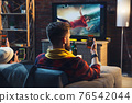 Group of friends watching TV, sport match together. Emotional fans cheering for favourite team, watching on exciting game. Concept of friendship, leisure activity, emotions 76542044