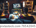 Group of friends watching TV, sport match together. Emotional fans cheering for favourite team, watching on exciting game. Concept of friendship, leisure activity, emotions 76542045