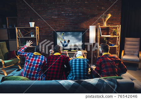 Group of friends watching TV, sport match together. Emotional fans cheering for favourite team, watching on exciting game. Concept of friendship, leisure activity, emotions 76542046