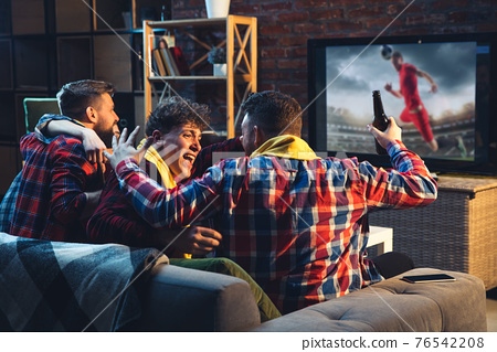 Group of friends watching TV, sport match together. Emotional fans cheering for favourite team, watching on exciting game. Concept of friendship, leisure activity, emotions 76542208