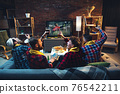 Group of friends watching TV, sport match together. Emotional fans cheering for favourite team, watching on exciting game. Concept of friendship, leisure activity, emotions 76542211
