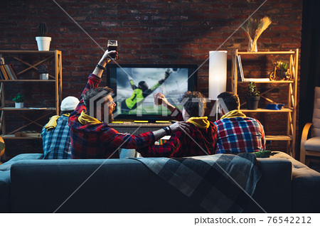 Group of friends watching TV, sport match together. Emotional fans cheering for favourite team, watching on exciting game. Concept of friendship, leisure activity, emotions 76542212
