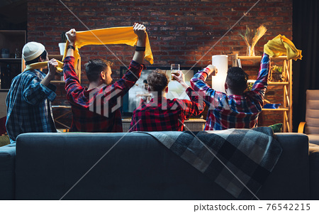 Group of friends watching TV, sport match together. Emotional fans cheering for favourite team, watching on exciting game. Concept of friendship, leisure activity, emotions 76542215