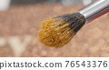 Brush gains glitter to be used in make-up. Macro view of working process, tools in beauty industry. Fashion glamour shiny glitter concept. 76543376