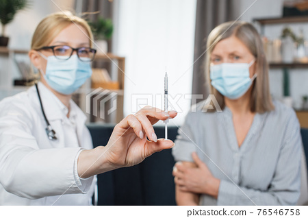 Blurred view of two women, doctor and patient, in protective masks, sitting together on the couch at home. Female doctor demonstrating syringe to camera, visiting patient for vaccination at home 76546758