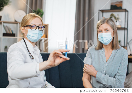 Front view of pleasant likable blond woman doctor, in face mask, holding a syringe with vaccine or medicine, ready to make an injection for her patient, senior lady. Home visit of the doctor 76546768