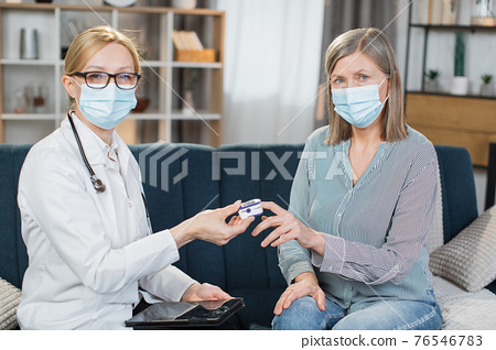 Home treatment of virus. Coronavirus pandemic. Covid-19 outbreak. Female blond doctor in face mask, examining sick patient, senior woman, measuring saturation level with pulse oximeter 76546783