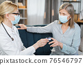 Close-up of female healthcare worker, doctor or nurse, using finger pulse oximeter, while visiting sick patient elderly woman at home, checking oxygenation level 76546797