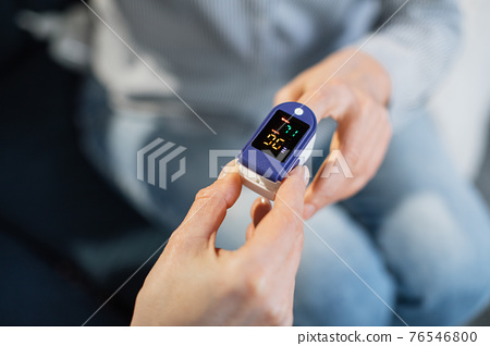 Pulse oximeter, finger digital device to measure oxygen saturation in blood. Close up view of doctor hand measuring oxygenation level of female unrecognizable patient for exclusion of pneumonia 76546800