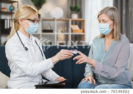 Blond female doctor in medical coat, glasses and protective mask, measuring oxygen saturation and heart rate with a pulse oximeter, while visiting her sick retired lady patient at home 76546882