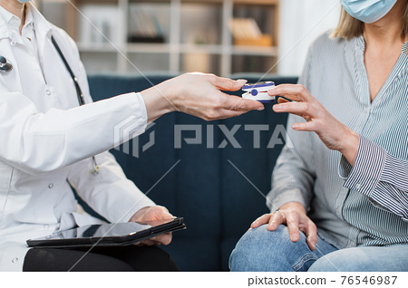 Closeup of unrecognizable female doctor examining senior patient in ptoective mask with fingertip pulse oximeter, during home visit for checking patient oxygen saturation 76546987