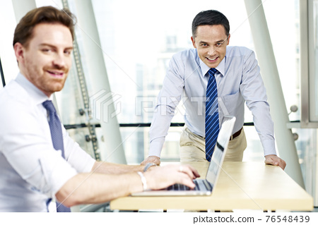 two caucasian business executives working in office looking at camera smiling 76548439