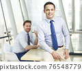 successful caucasian business leader sitting on desk in office smiling with colleague in background 76548779