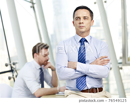 caucasian businessman sitting on desk arms crossed thinking in office with colleague in background 76549125