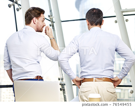 rear view of two caucasian business people looking out of window talking in office 76549455