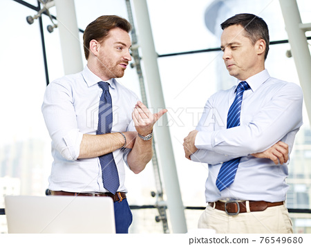 two caucasian business persons standing and chatting in office 76549680