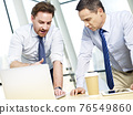 two caucasian business executives working together using laptop computer in office 76549860