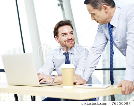 businessmen working together on laptop computer 76550097