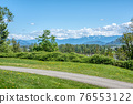 Riverbank walkway with overview of snow caps on Rocky mountains 76553122